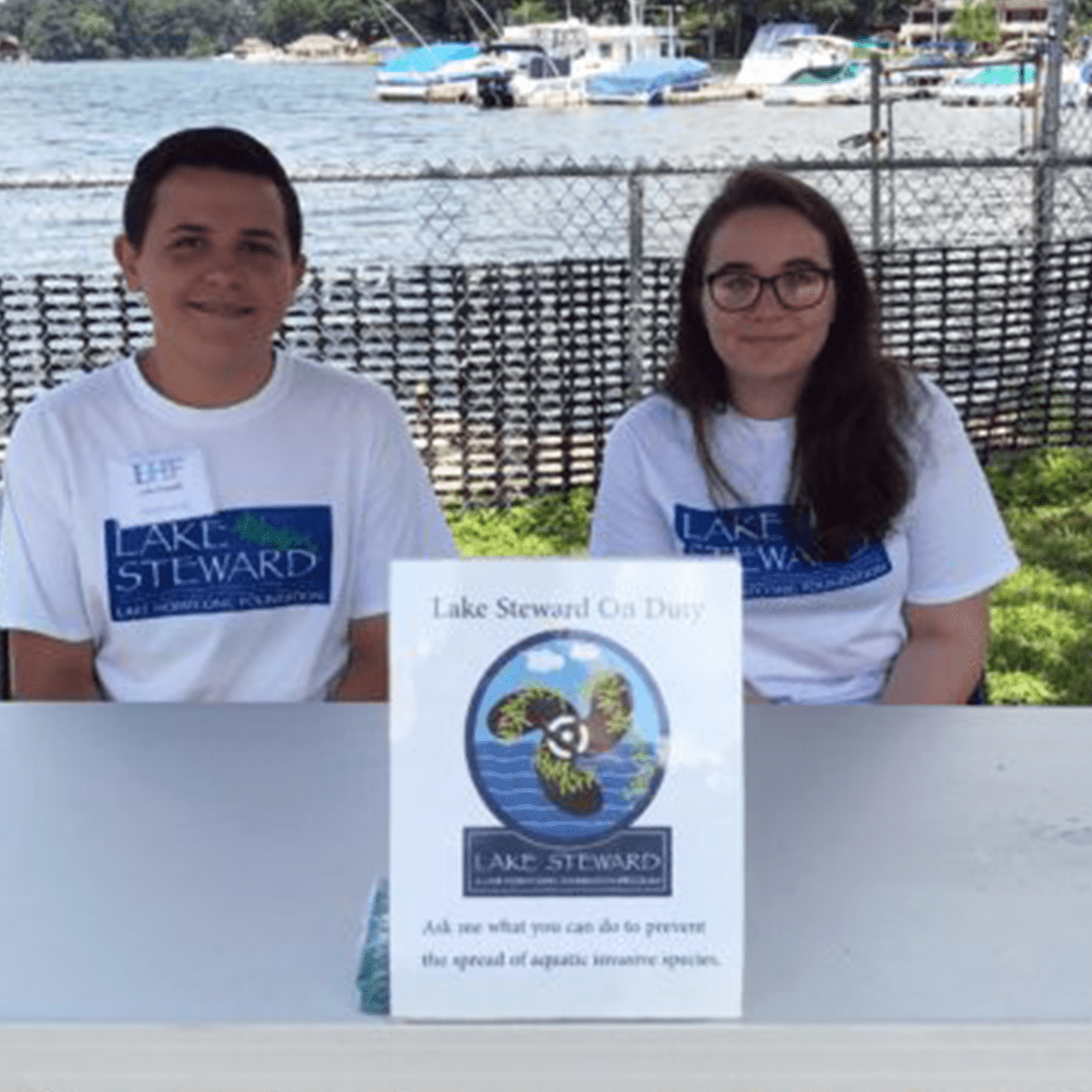 Two teenagers posing at their Lake Steward Program booth