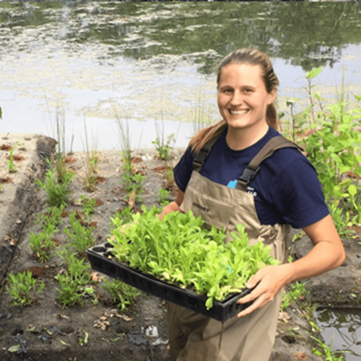 A young woman posing with her flat of aquatic plants
